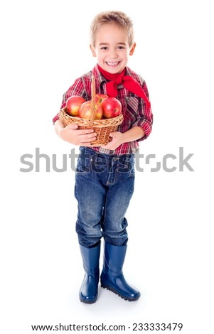 Little farmer boy holding wicker basket basket with apples - stock photo