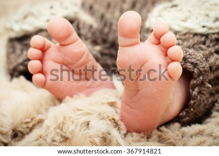 Little feet of a newborn child - stock photo