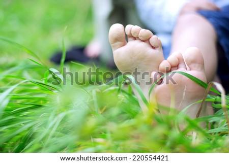 Little feet on the grass - stock photo