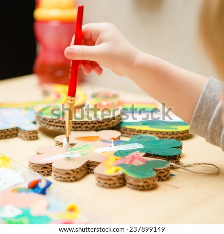 Little female baby painting with colorful paints. selective focus - stock photo