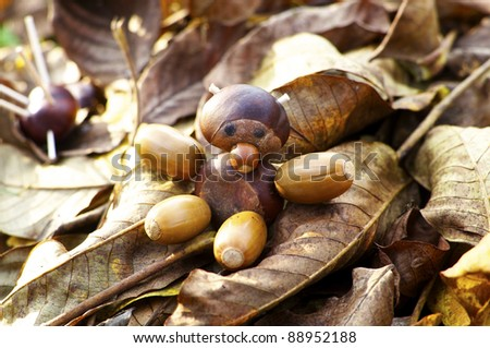 Little figure of a teddybear made of chestnuts, oaks and a hazelnut sitting on fallen leaves - stock photo