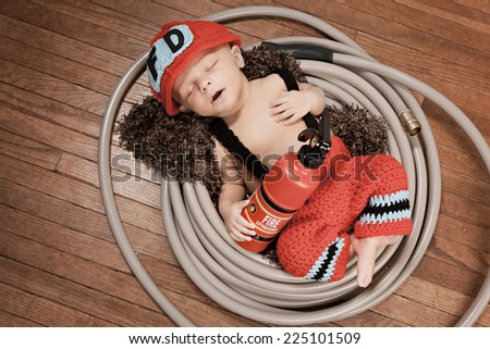 Little fireman.  Adorable infant dressed as a fireman and asleep in a garden hose holding a toy fire extinguisher.  room for your text. - stock photo