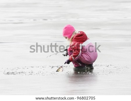 Little fisherman catching a fish on ice. - stock photo