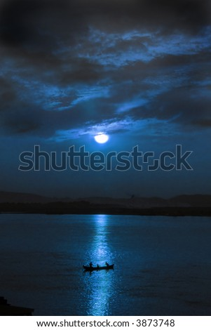 little fishing boot on the river at night lit by the full moon - stock photo