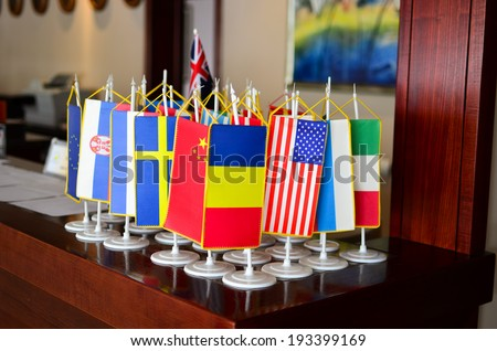 Little flags of different counties on the reception desk in a hotel  - stock photo