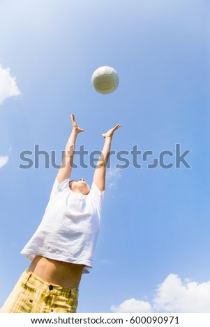 little football player jumping for the ball against the blue sky