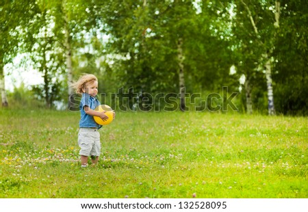 little football player standing on the field and holding yellow ball - stock photo