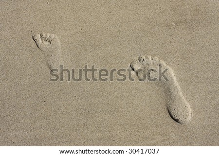 Little footprint and big footprint in Sand - stock photo