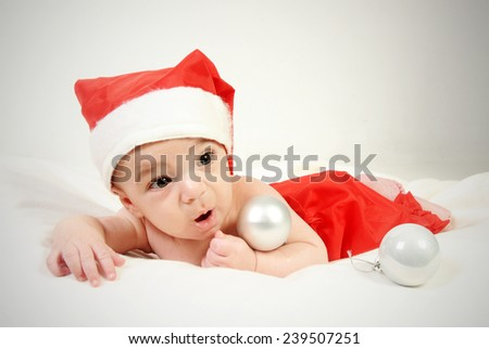 little four month old baby boy wearing red santa hat and red trousers lying on his belly with a surprised expression on his face playing with silver Christmas tree decorative balls