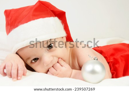 little four month old baby boy wearing red santa hat and red trousers lying on his belly with his hand in his mouth playing with silver Christmas tree decorative balls - stock photo