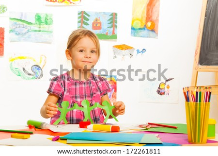 Little four years old girl holding garland made of paper in art class in kindergarten - stock photo