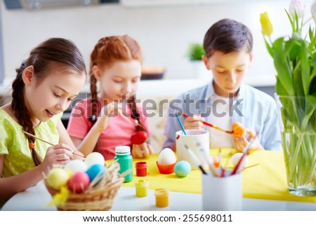 Little friends painting Easter eggs before holiday - stock photo