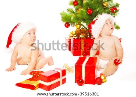 Little friends  sitting beside Christmas tree - stock photo