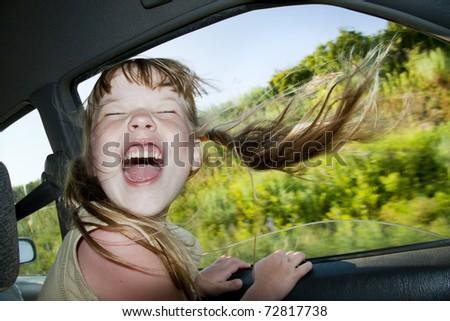 Little fun girl speeds in car near the open window. - stock photo