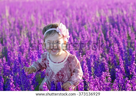 Little funny baby girl smiling in a purple flowers field