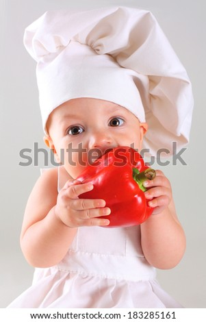 Little funny baby in a cap chef with Pepper - stock photo