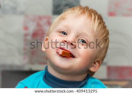 Little funny baby is eating sausage and smiling.