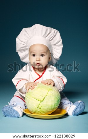 little funny baby with cook costume holds cabbage - stock photo