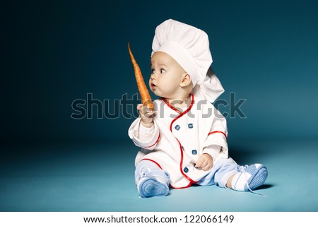 little funny baby with cook costume holds carrot - stock photo