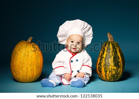 little funny baby with cook costume holds pumpkin - stock photo