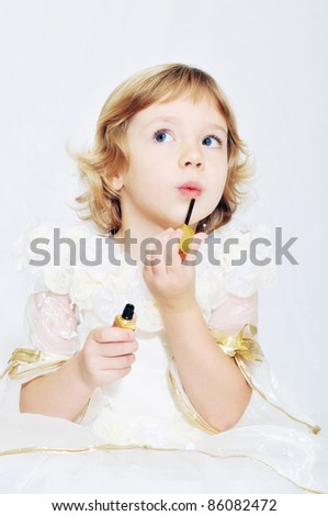 little funny blonde girl playing with lipstick - stock photo