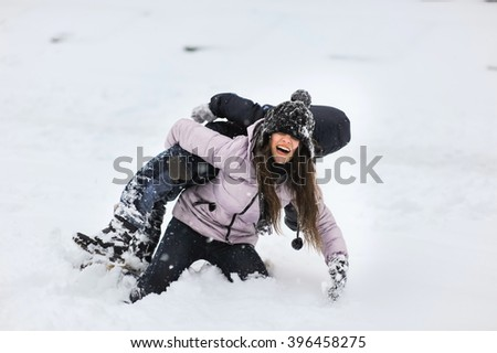Little funny boy and young girl having fun with snowballs during snowfall. Active outdoors leisure with children in winter. Children, kids, friends, brother and sister playing with snow in park. - stock photo