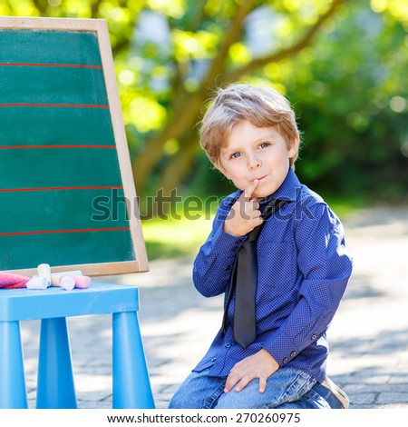 Little funny boy at blackboard thinking about mathematics, outdoor school or nursery. Kid learning and schoolboy concept. On summer sunny day.