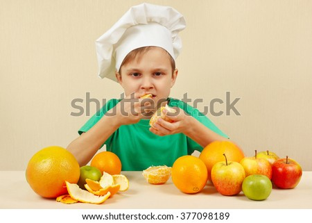 Little funny boy eat fresh orange at the table with fruits