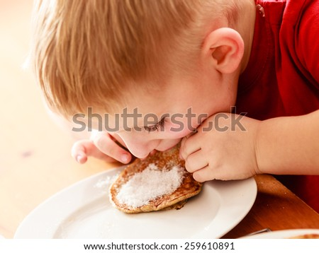 Little funny boy eating with relish mael fried apple in pancake dough or apple fritters pancakes with icing sugar at home - stock photo
