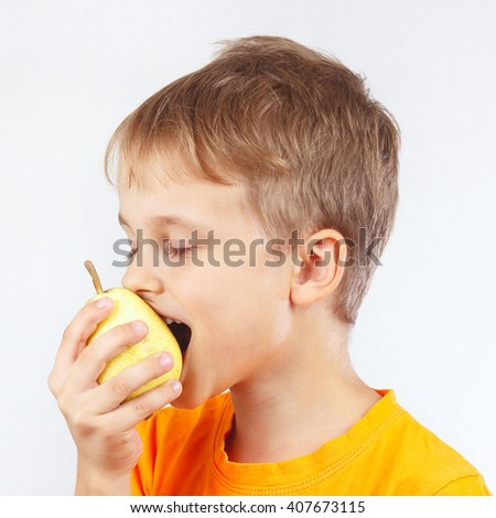 Little funny boy in a orange shirt eating a ripe yellow pear - stock photo