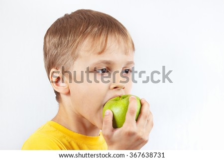 Little funny boy in a yellow shirt eating a green apple