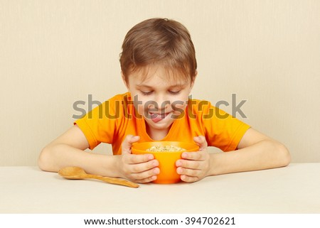 Little funny boy is going to eat cereal - stock photo