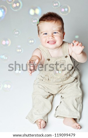 little funny boy plays with bubbles