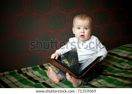 little funny boy reading book at home - stock photo