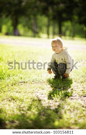 little funny boy sitting in grass - stock photo