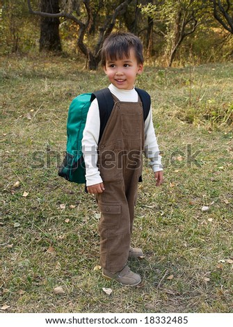 Little funny boy stands with backpack just come back from school