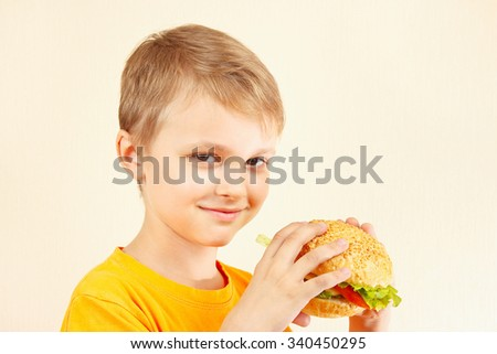 Little funny boy with a tasty sandwich - stock photo