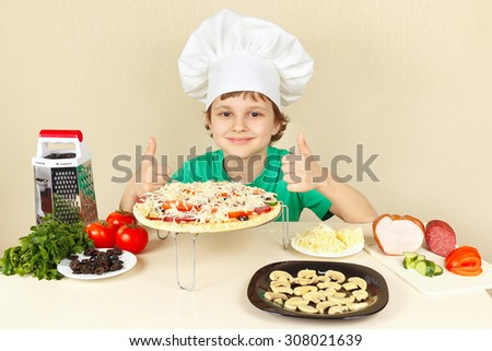 Little funny chef in chefs hat enjoys a cooking tasty pizza - stock photo