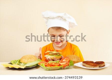 Little funny chef in chefs hat preparing a hamburger - stock photo