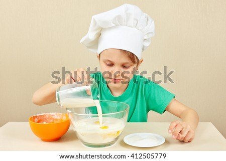 Little funny chef pours milk for baking the cake - stock photo