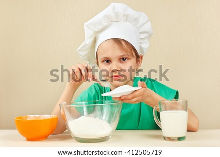 Little funny chef pours sugar for baking the cake - stock photo