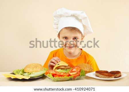 Little funny chef puts cheese on the hamburger - stock photo