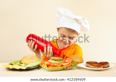 Little funny chef puts ketchup on the hamburger - stock photo