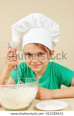 Little funny chef shuffles dough for baking the cake - stock photo