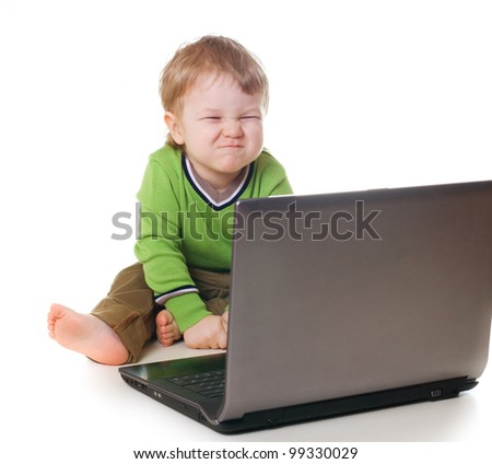 Little funny child using a laptop - stock photo