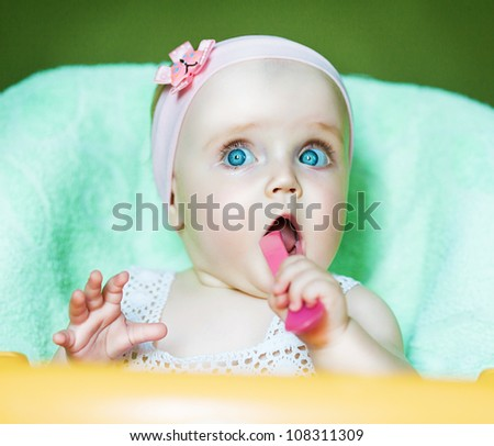 little funny child with pink spoon in mouth - stock photo
