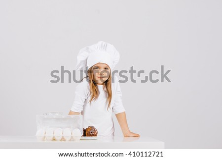 Little funny girl in a suit chef in the kitchen with milk and cakes on a white background