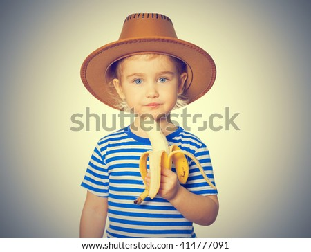 Little Funny girl in striped shirt and hat eats banana. Isolated on gray background - stock photo