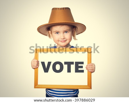 Little Funny girl in striped shirt with blackboard. Text VOTE.  Isolated on gray background. - stock photo