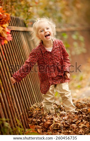 little funny girl is standing near the fence and laughing in the park in autumn - stock photo